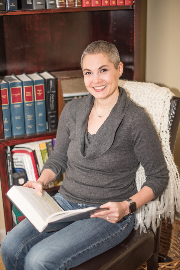 Attorney sitting in front of book case, reading law book.